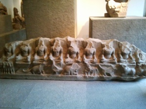 Bas relief représentant 9 divinités. Retrouvé dans les fouilles aux environs de Huế, ce bloc est une œuvre magistrale du 12è siècle. Les 9 dieux brahmaniques sont représentés dans une posture assise, accompagnés de leurs animaux symboliques. A l'extrême gauche nous avons Surya, dieu du soleil. Il a quatre femmes : la connaissance, la souveraineté, la lumière et l'ombre. Soma, dieu de la lune, est représenté avec le guépard, animal doté d'une remarquable vélocité qui peut sauver l'homme de la mort. Vaya, dieu du vent, est accompagné de l'antilope. Gardien du nord-ouest, il est le souffle invisible qui se déplace incognito librement.
